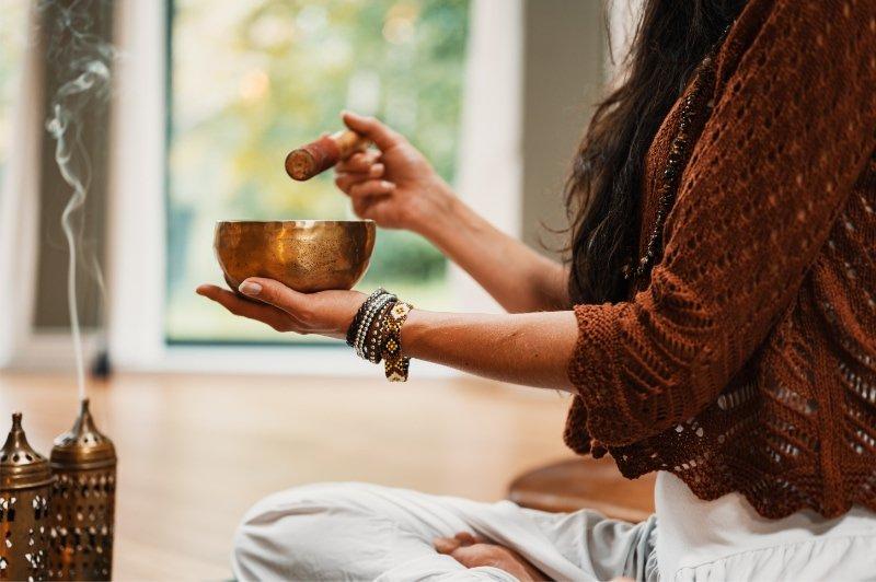 Una donna si prepara per la meditazione di fine anno in casa con incenso e campana tibetana