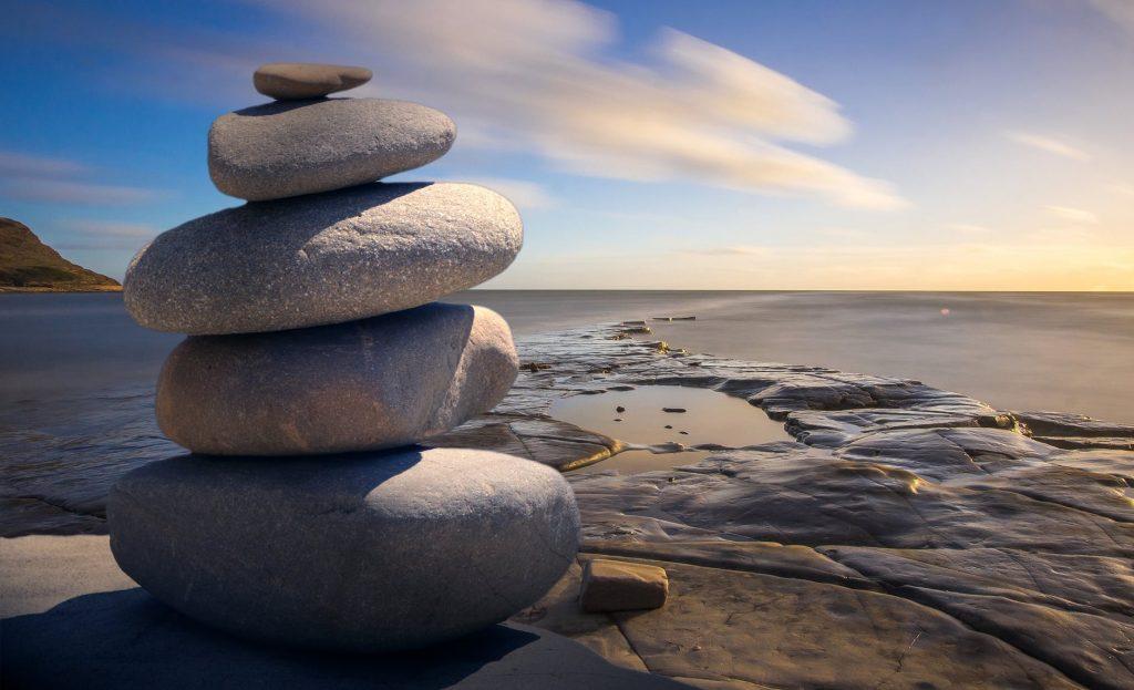Un ometto di pietre e sassi impilati uno sopra all'altro sulla riva simbolaggiano la meditazione mindfulness