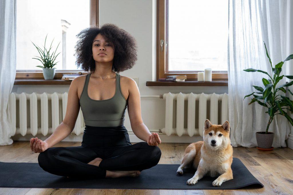 Ragazza che pratica tecniche di respirazione yoga in compagnia del suo cane